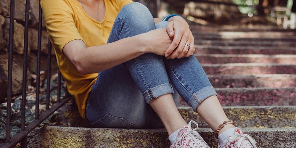 Kvinna sitter i trappa och håller armarna om sina ben.